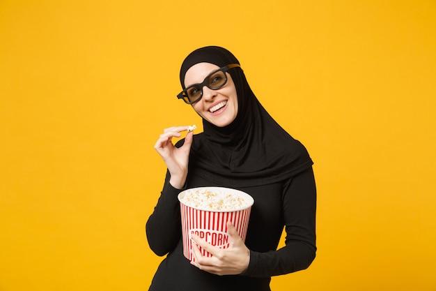 Muslimische frau in hijab schwarzer kleidung 3d-imax-brille filmfilm halten eimer popcorn, essen popcorn isoliert auf gelbem wandporträt. menschen lifestyle-konzept. .