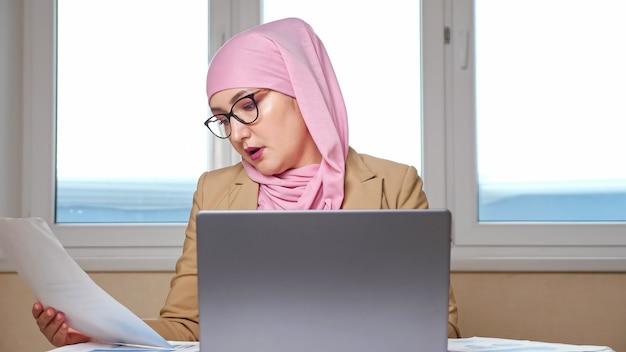 Muslimische frau in rosa kopftuch und brille, die am laptop und mit dokumenten arbeitet.