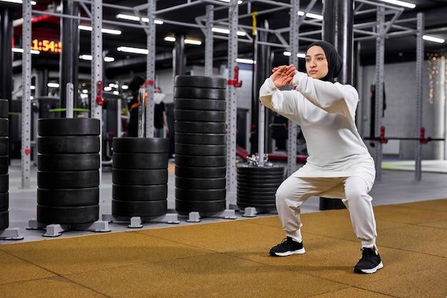 Muslimische frau ist im sport tätig. junge arabische frau, die im modernen fitnessstudio trainiert und weißen sportlichen hijab trägt. sport, fitness, stretching-konzept
