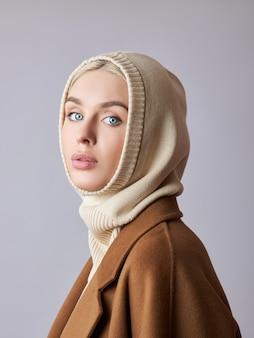 Muslimische frau mit blonden haaren in einem kopftuchschal auf dem kopf.