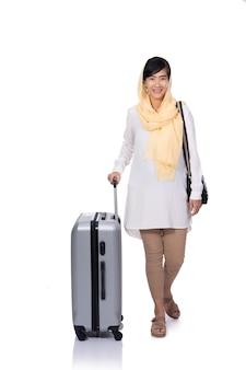 Muslimische frau mit dem koffer, der zur kamera lächelt