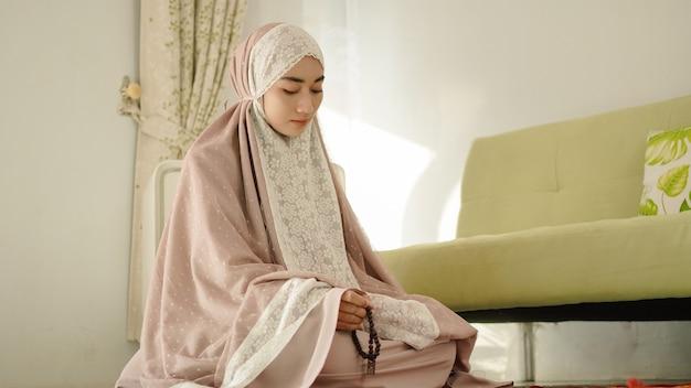 Muslimische frau mit gebetskette für dhikr nach der durchführung von salat