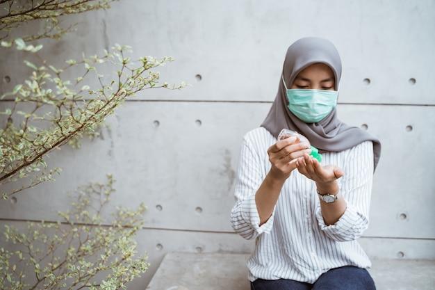 Muslimische frau mit händedesinfektionsgel