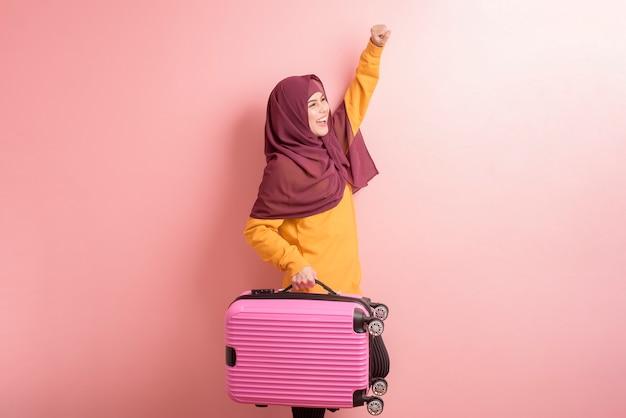 Muslimische frau mit hijab hält gepäck auf rosa hintergrund, leute reisen konzept
