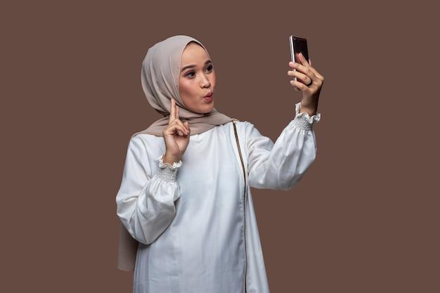 Muslimische frau mit hijab macht ein selfie mit einem smartphone