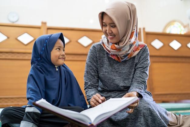 Muslimische frau mit kindern, die zusammen koran lesen