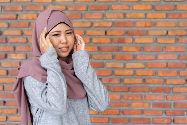 Muslimische frau mit kopfschmerzen