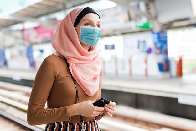 Muslimische frau mit maske auf dem bahnsteig