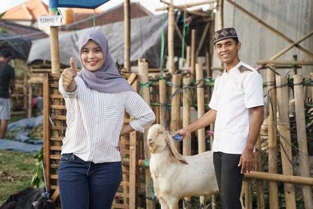 Muslimische frau mit schal, der daumen oben zeigt, während er in der ziegenfarm steht. eid adha konzept