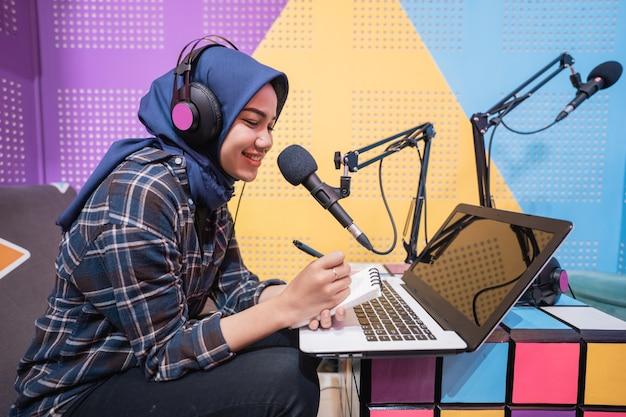 Muslimische frau nimmt einen podcast im studio mit laptop auf und macht eine notiz mit stift