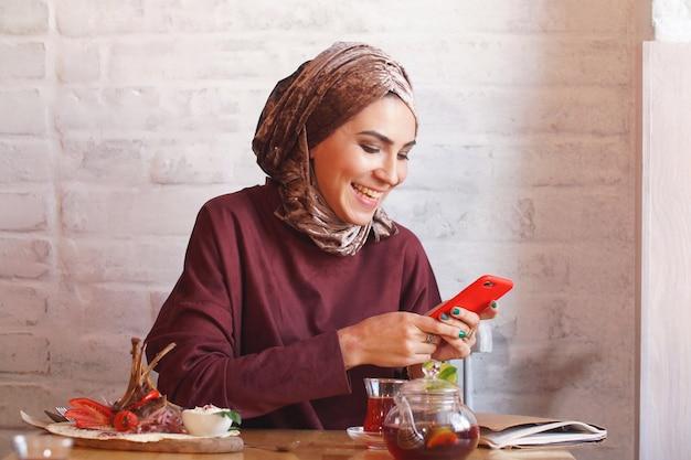 Muslimische frau sitzt in einem café und benutzt das telefon für die korrespondenz