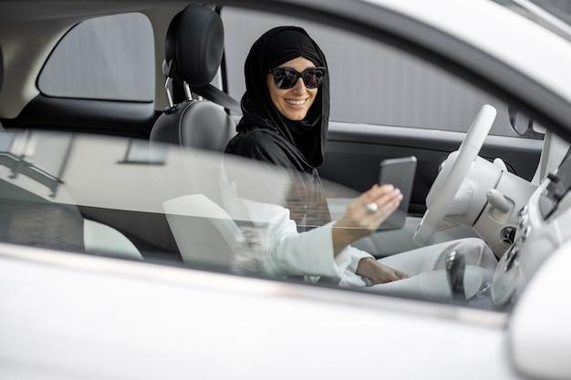 Muslimische frau telefoniert beim autofahren