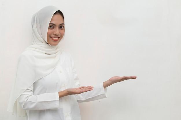 Muslimische frau trägt hijab lächelnd und zeigt mit den fingern in verschiedene richtungen. kopieren sie den platz für werbung