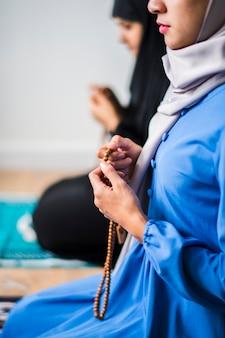 Muslimische frauen benutzen misbaha, um in tasbih zu zählen