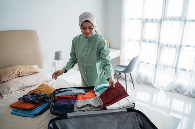 Muslimische frauen, die hijabs tragen, bereiten kleidung für den koffer vor