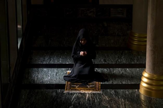 Muslimische frauen, die schwarze hemden tragen gebet gemäß den prinzipien des islam.