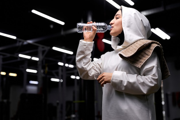 Muslimische frauen haben ruhe nach einem harten training, trinken frisches wasser, genießen freizeit, lieben es, gesund zu sein. sportkonzept