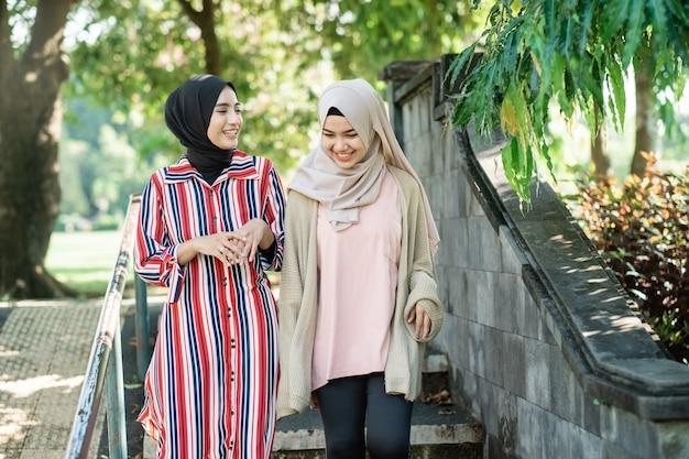 Muslimische frauen in hijabs im freien am sonnigen tag mit freund glücklich