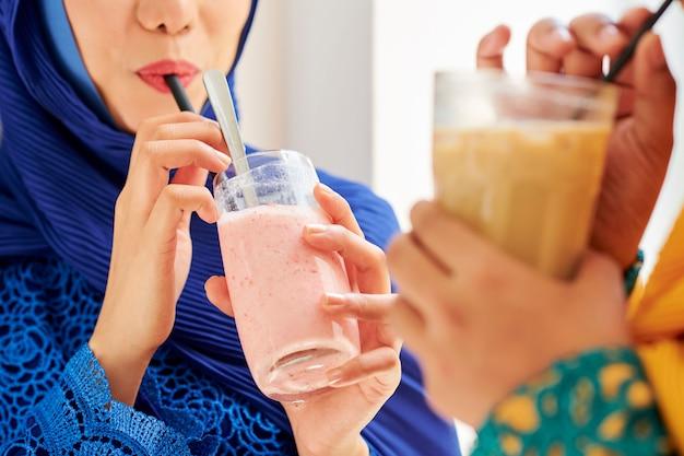 Muslimische frauen trinken fruchtsmoothie