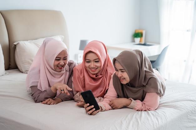 Muslimische frauen und freunde, die auf dem bett glücklich aussehendes smartphone liegen
