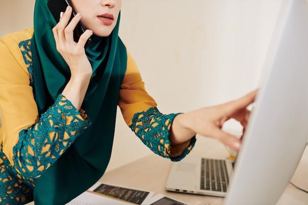 Muslimische geschäftsdame, die am telefon spricht