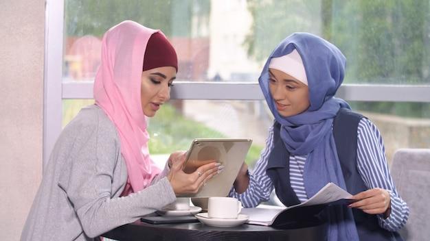 Muslimische geschäftsfrau bei einem geschäftstreffen in einem café.
