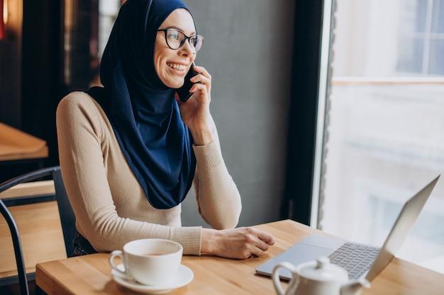 Muslimische geschäftsfrau, die in einem café am computer arbeitet