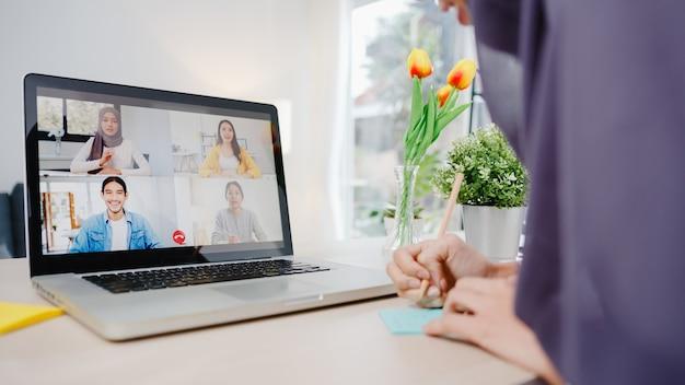 Muslimische geschäftsfrau, die laptop verwendet, gespräch mit kollegin über plan per videoanruf, brainstorming-online-meeting, während sie von zu hause aus im wohnzimmer arbeitet