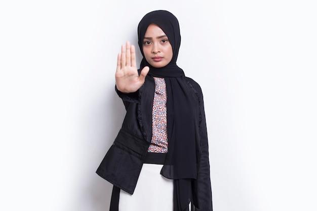 Muslimische geschäftsfrau mit offener hand macht stoppschild mit ernster ausdrucksverteidigungsgeste