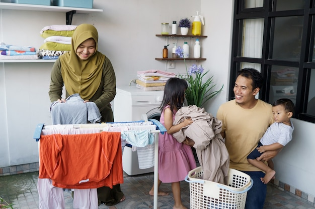 Muslimische glückliche familie, die wäsche zu hause zusammen macht