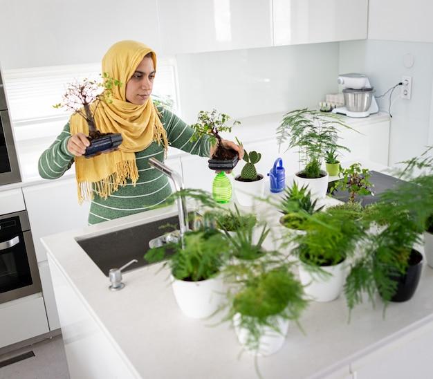 Muslimische hausfrau zu hause bewässerungspflanzen in der küche