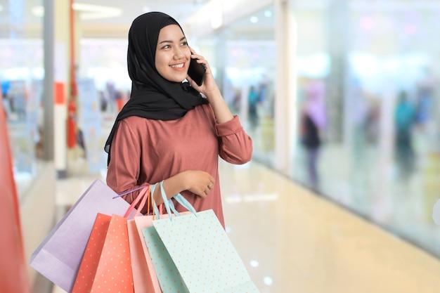 Muslimische junge einkaufsfrau telefonieren, während sie eine papiertüte im einkaufszentrum hält
