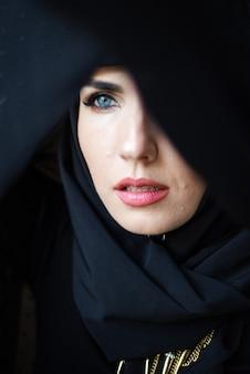 Muslimische junge frau auf dunklem hintergrund mit schwarzem hijab