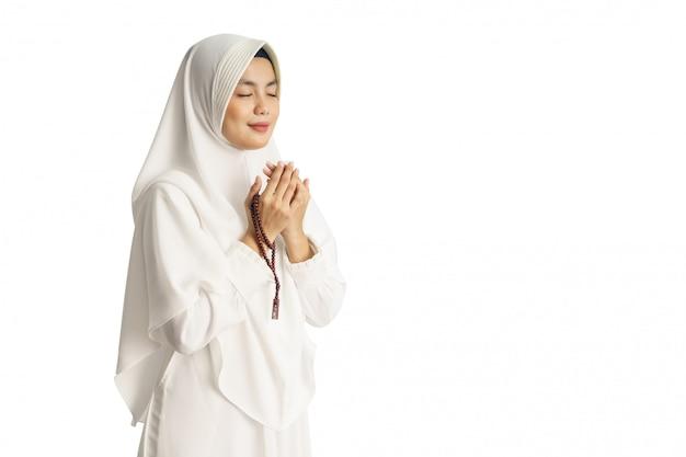 Muslimische junge frau, die betet, öffnet ihren arm