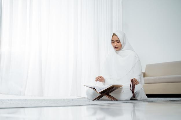 Muslimische junge frau, die in weißen traditionellen kleidern betet
