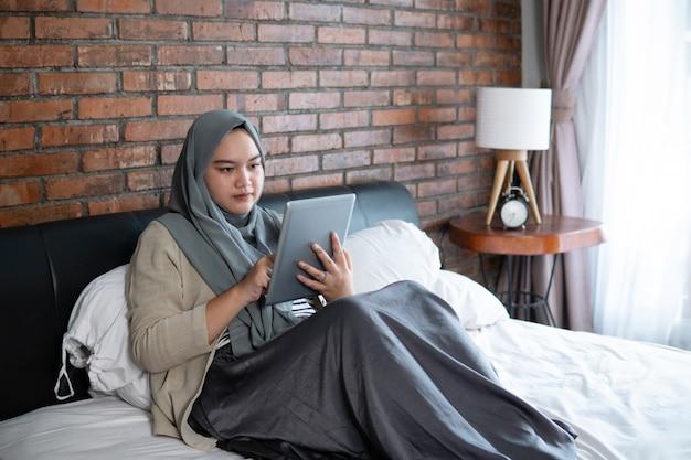Muslimische junge frau, die tablet-reservierungskarte verwendet