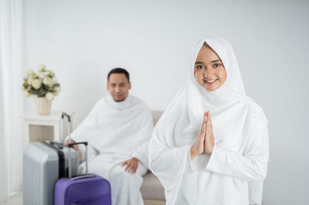 Muslimische junge frau, die vor ihrem ehemann vor umrah steht