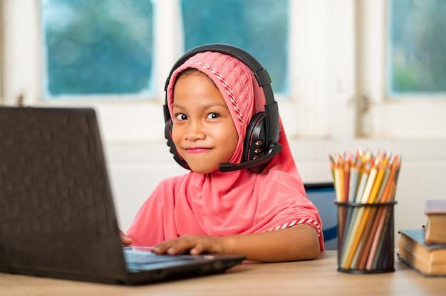 Muslimische mädchen, die zu hause online lernen um soziale distanz zu verringern und übertragbare krankheiten zu verhindern