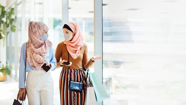 Muslimische mädchen hängen in gesichtsmasken im einkaufszentrum