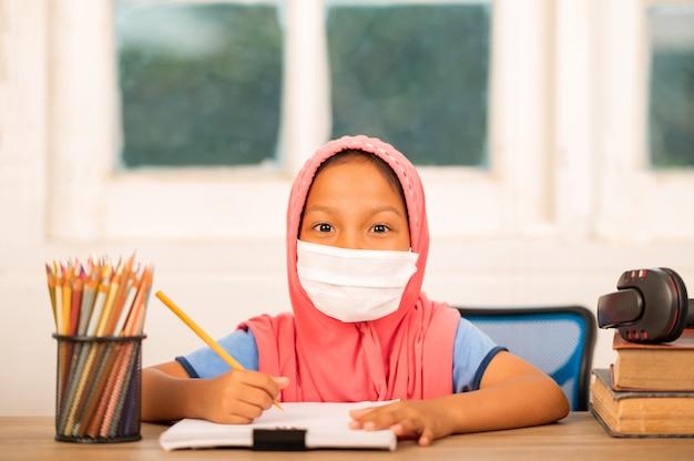 Muslimische mädchen mit hygienemasken, die zu hause online lernen um soziale distanz zu verringern und übertragbare krankheiten zu verhindern