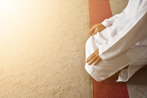 Muslimische männer, die in tashahhud-haltung beten