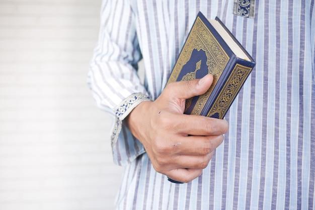 Muslimische mannhand mit heiligem buchkoran mit kopienraum