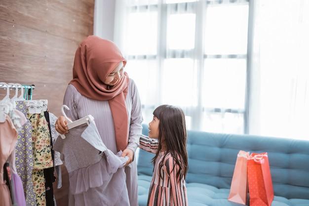 Muslimische mutter beim einkaufen mit ihrer tochter im boutique-bekleidungsgeschäft