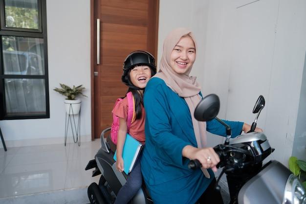 Muslimische mutter bringt ihre tochter morgens mit dem motorrad zur schule. asiatischer grundschüler zurück zur schule