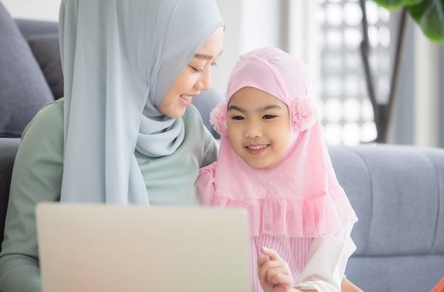 Muslimische mutter, die mit laptop und niedlichem kleinen baby arbeitet, das spielzeug im wohnzimmer zu hause spielt.