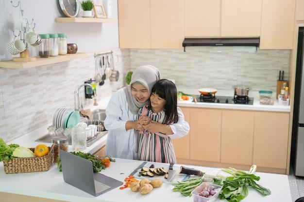 Muslimische mutter, die rezept vom laptop betrachtet und mit ihrer tochter kocht. spaß haben frau mit hijab und kind, die abendessen zusammen vorbereiten