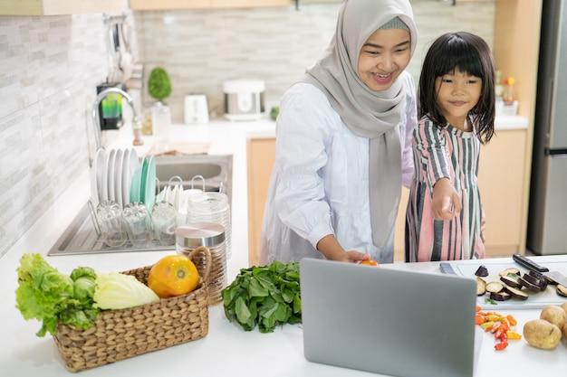 Muslimische mutter, die rezept vom laptop betrachtet und mit ihrer tochter kocht. spaß haben, frau mit hijab und kind, die gemeinsam das abendessen zubereiten