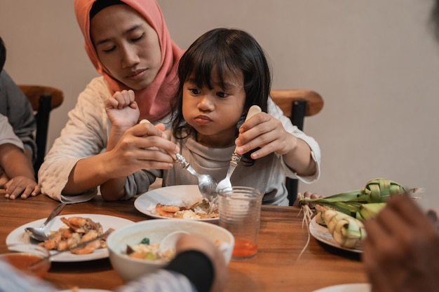 Muslimische mutter essen mit ihrer tochter, die auf schoß sitzt
