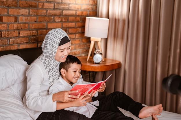 Muslimische mutter liest mit ihrem sohn ein buch