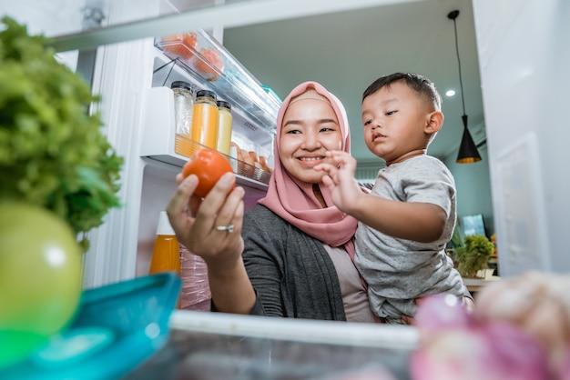 Muslimische mutter und sohn öffnen den kühlschrank zu hause auf der suche nach einem essen aus dem kühlschrank